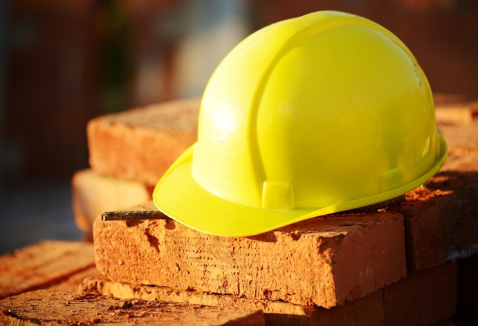 construction-hat-laying-across-bricks