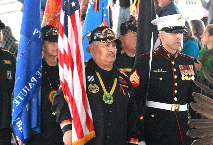 Native Veterans with flags in military attire
